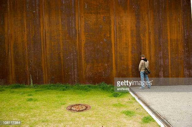 Man Urinating Outside on Rusty Wall Near Green Grass