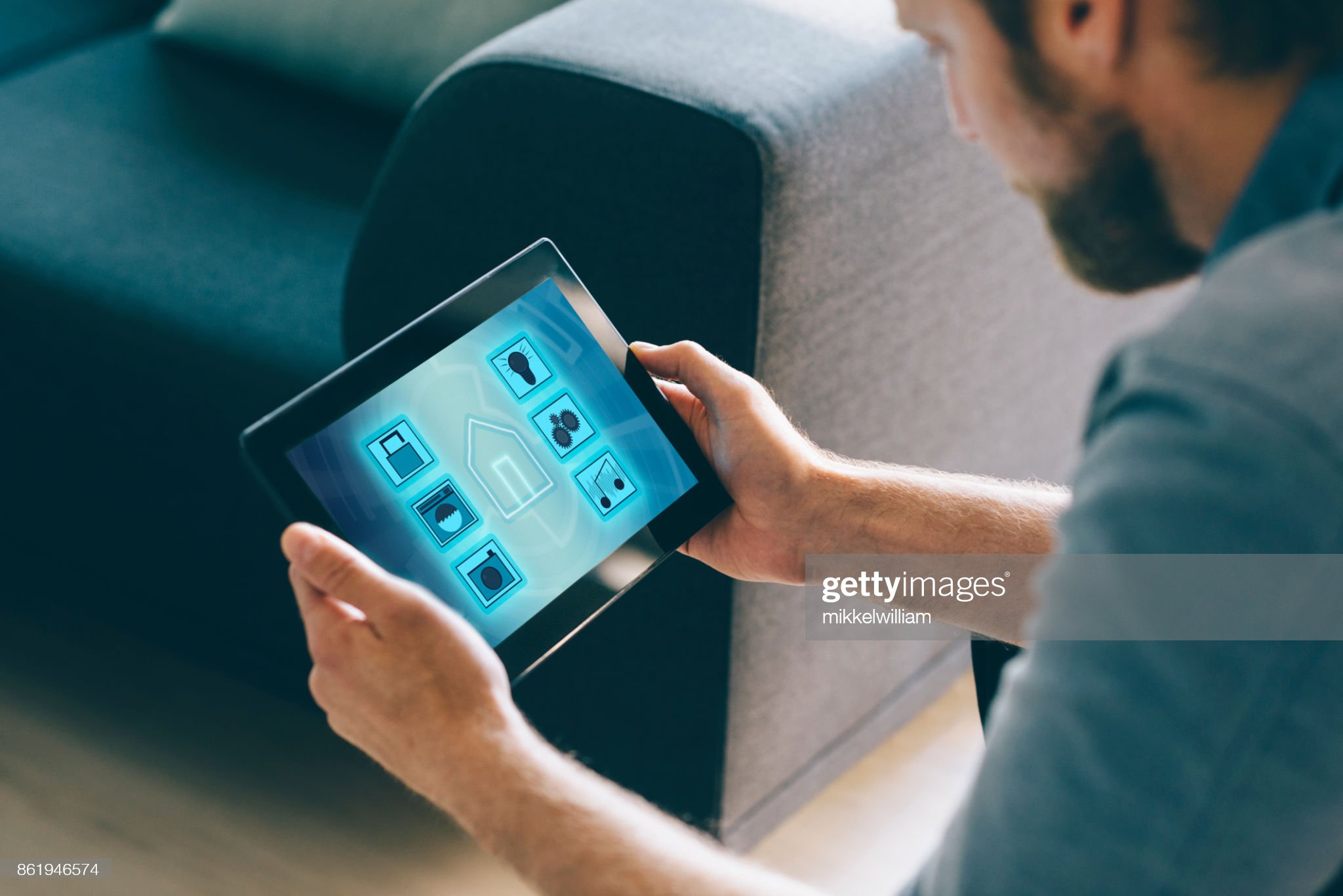 Man use smart home automation in living room with digital tablet and mobile app : Stock Photo