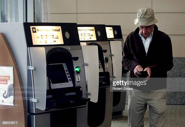 A man uses a bank machine at the Washington Mutual building the morning after it was seized by the FDIC and then sold to JP Morgan Chase September 26...