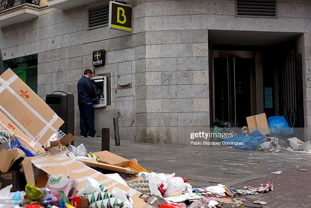 A man uses a bank's cash machine as litter covers the entrance and lines the street in the city centre on November 10, 2013 in Madrid, Spain. Street cleaners, garbage collectors and public park gardeners working for Madrid city council started an indefinite strike six days ago. Franchise firms which employ them plan to axe more than 1,000 jobs and those who will remain will have to face working for a 40 percent cut in their wages.