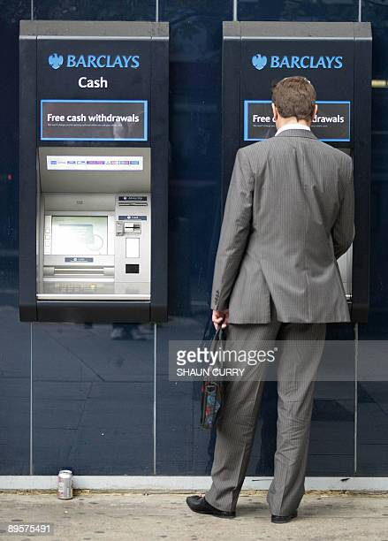 A man uses a Barclays bank ATM machine in central London on August 03 2009 British banking giant Barclays announced Monday that firsthalf net profits...