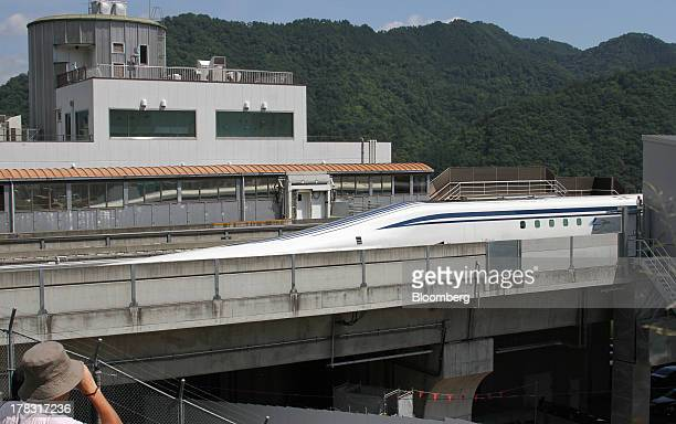 A man uses a binocular to look at the L0 series magneticlevitation train developed by Central Japan Railway Co moving along a test track during a...