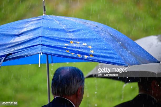 A man uses a broken umbrella with the logo of the European Union to protect against the pouring rain on June 29 2017 at the Chancellery in Berlin...