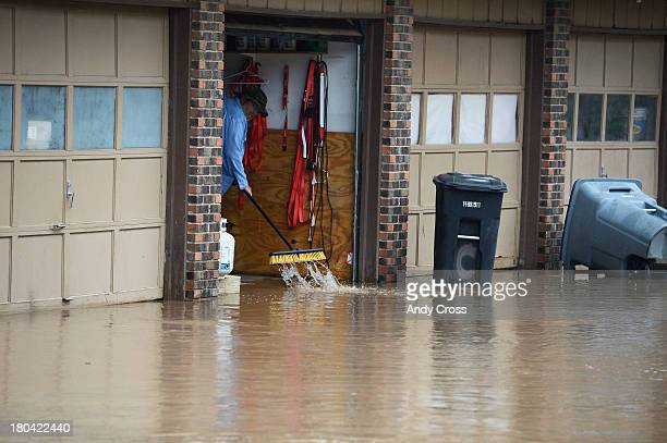 A man uses a broom to try and get water out of his garage in Longmont Colorado Thursday morning September 12 2013 The water came from heavy rain but...