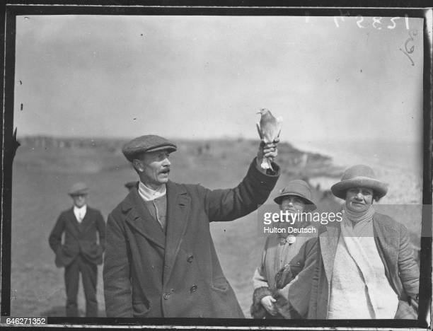 A man uses a carrier pigeon to spread the results of the Deal amateur golf championship