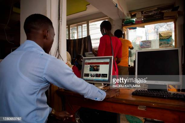 Man uses a computer to read news at a cyber cafe minutes after the Uganda Communication Commission, a body responsible for communications in Uganda,...