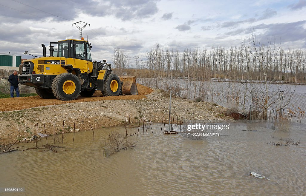 A man uses a digger to build a dam following the rise of the River Ebro due to heavy rainfall in Boquianeri, near Zaragoza, on January 22, 2013.