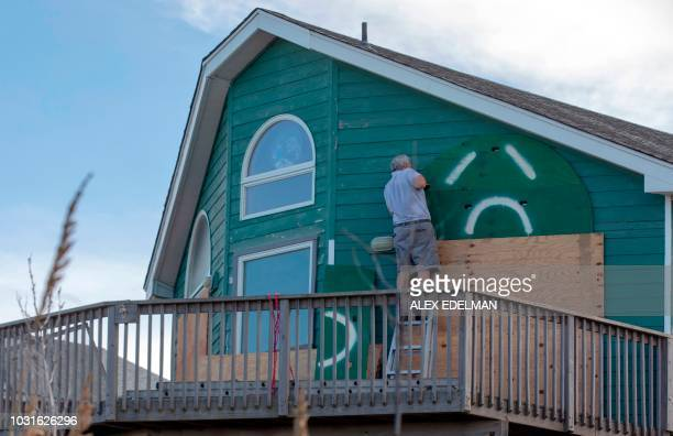 A man uses a drill to install storm shutters on a home in Kill Devil Hills in the Outer Banks of North Carolina on September 11 2018 Streams of cars...
