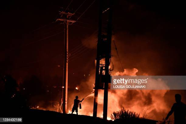 Man uses a fire extinguisher as local residents try to fight the forest fire in Dekelia, north of Athens, on August 3, 2021. - A forest fire broke...
