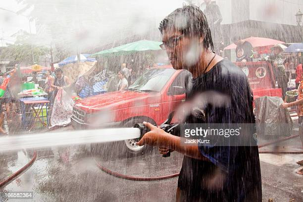 A man uses a fire hose against his opponents during a community water fight on Silom Road as part of the Songkran water festival on April 14 2013 in...