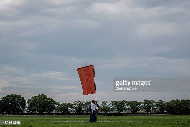 A man uses a flag to mark a starting point for a parade during the Soma Nomaoi festival at Hibarigahara field on July 25 2015 in Minamisoma Japan...