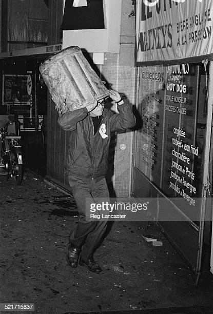 A man uses a garbage bin to protect his head during civil unrest in Paris France 30th May 1968