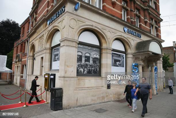 A man uses a gold coloured automated teller machine outside a branch of British bank Barclays in Enfield north London on June 27 on he 50th...