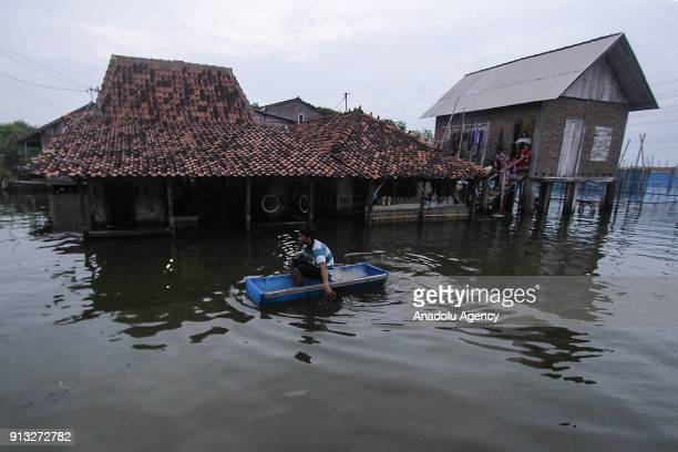A man uses a handmade boat to reach his waterlogged home in Sriwulan village Sayung subdistrict of Demak regency Central Java Indonesia on February 2...