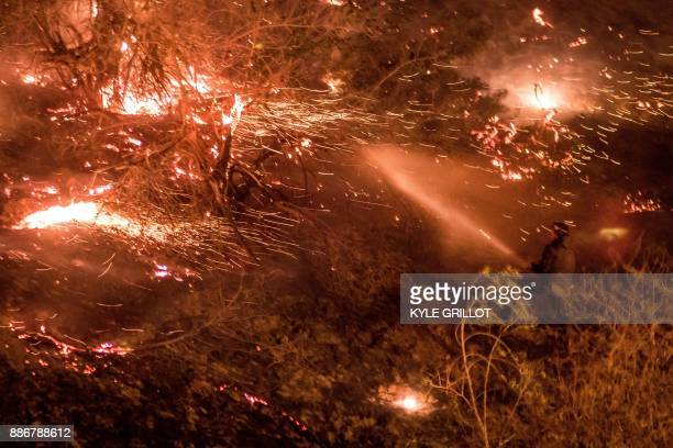 TOPSHOT A man uses a hose to extinguish the Creek Fire as it burns along a hillside near homes and horses in the Shadow Hills neighborhood of Los...