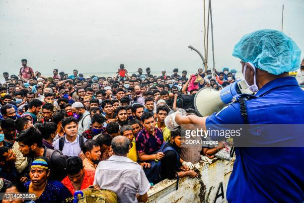 Man uses a loud speaker to address migrant people on an overcrowded ferry. Migrants flock at the Shimulia-Kathalbari ferry terminal in Munshiganj...