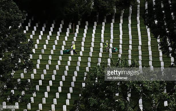 A man uses a machine among rows of graves as landscape professionals volunteer their time to help beautify more than 200 acres at Arlington National...
