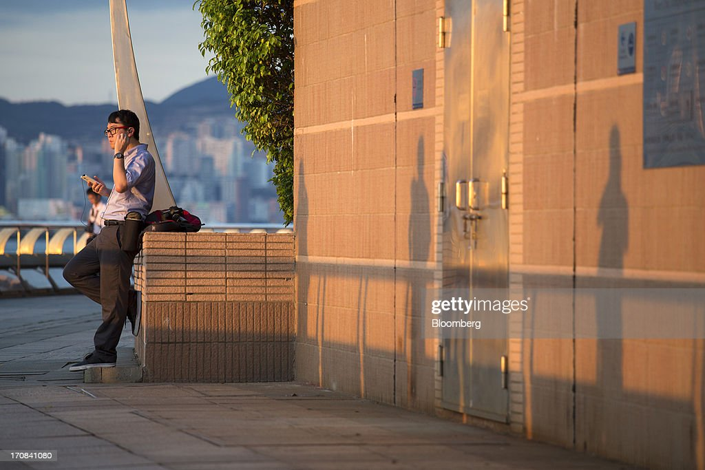 A man uses a mobile device as he leans against a wall near Golden Bauhinia Square in Hong Kong, China, on Tuesday, June 18, 2013. A shortage of housing, low mortgage costs and a buying spree by mainland Chinese have led home prices to more than double since the beginning of 2009, shrugging off repeated attempts by the government to curb gains amid an outcry over affordability. Photographer: Jerome Favre/Bloomberg via Getty Images