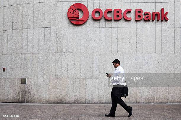 A man uses a mobile device as he walks past signage for OverseaChinese Banking Corp displayed at the OCBC Center building in Singapore on Friday Aug...
