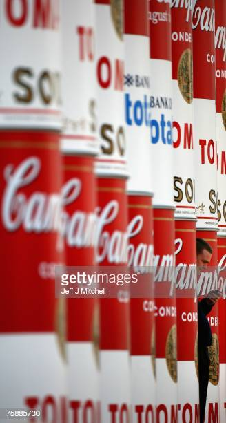 Man uses a mobile phone as he stands between enlarged Campbell's soup cans that are wrapped around the columns of the National Gallery of Scotland to...