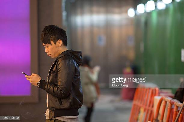 A man uses a mobile phone as he stands by the side of a road in Hong Kong China on Friday Jan 4 2013 Chief Executive Leung Chunying who has been...