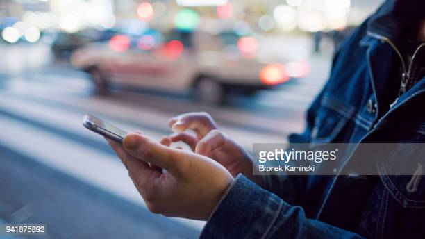 a man uses a mobile phone at shibuya crossing - sms'en stockfoto's en -beelden