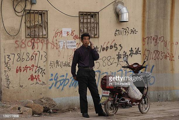 Man uses a mobile phone in front of a wall covered in mobile phone numbers in Hohhot in China's Inner Mongolia region on April 14, 2009. China is the...