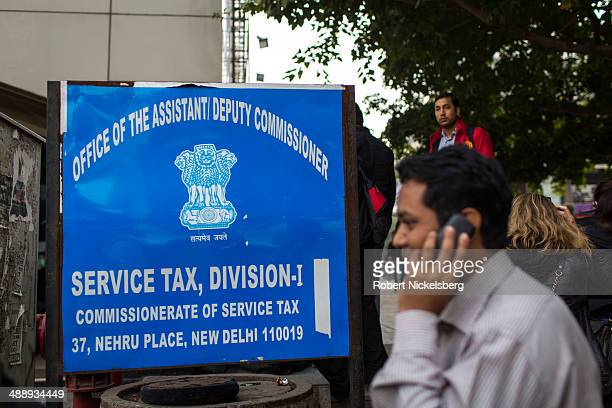 A man uses a mobile phone in front of the federal government excise and service tax office March 1 2014 in New Delhi India