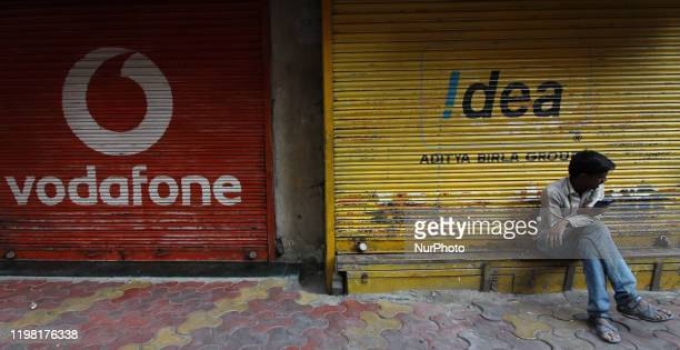 Man uses a mobile phone outside the downed shutters of a shop painted with a logo of Vodafone in Mumbai, India on 02 February 2020.