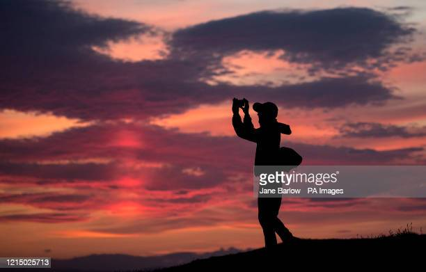 A man uses a mobile phone to take a picture of the sunset from Calton Hill Edinburgh