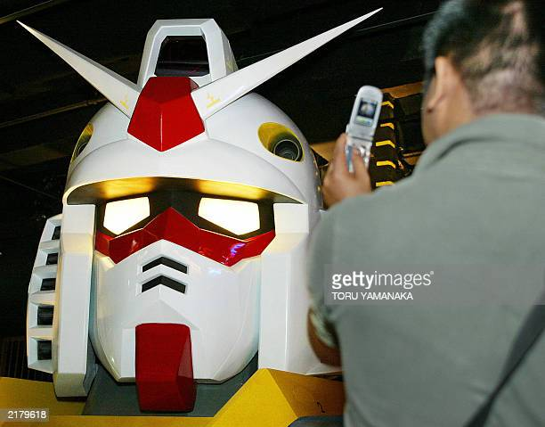 A man uses a mobile phone to take pictures of a 56meter actual size bust of TV animation hero 'Gundam' displayed at the Bandai Museum in Matsudo...