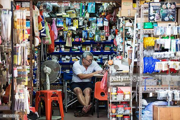 A man uses a mobile phone while working at a hardware store in the area of Chinatown in Singapore on Tuesday Jan 6 2015 In a culture that...