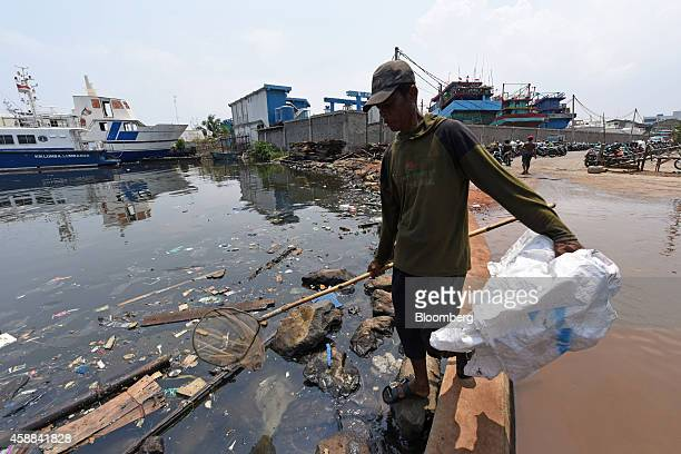 A man uses a net to collect waste from the water at a fishing port in the Muara Baru area of North Jakarta Indonesia on Wednesday Nov 5 2014 Jakarta...