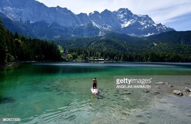 A man uses a paddle board on the Eibsee lake on May 25 2018 in Grainau southern Germany / Germany OUT