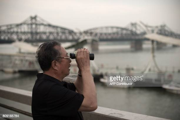 A man uses a pair of binoculars next to the Friendship bridge on the Yalu River connecting the North Korean town of Sinuiju and Dandong in Chinese...