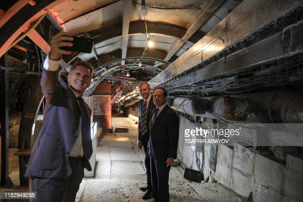 A man uses a phone to take a selfie photo inside an ancient tunnel during the opening of an ancient road at the City of David archaeological and...