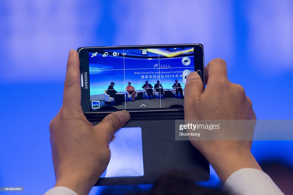 A man uses a Samsung Electronics Co. mobile device to take a photograph during a session at the Boao Forum for Asia in Boao, Hainan, China, on Thursday, April 10, 2014. The Boao Forum for Asia takes place from April 8-11. Photographer: Brent Lewin/Bloomberg via Getty Images