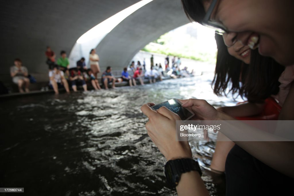 A man uses a Samsung Electronics Co. smartphone at Cheonggye Stream in Seoul, South Korea, on Wednesday, July 3, 2013. Samsung Electronics lost $25.3 billion in market capitalization last month, more than the value of competitor Sony Corp., as sales of its flagship Galaxy S4 smartphone fell short of investor expectations. Photographer: Woohae Cho/Bloomberg via Getty Images