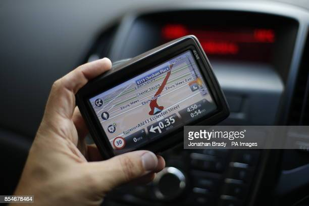 A man uses a satellite Navigator in his car The sat nav system s a system of satellites that provide autonomous geospatial positioning with global...