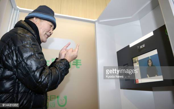 A man uses a sign language phone system installed in a building near JR Akashi Station in Hyogo Prefecture on Feb 5 2018 ==Kyodo
