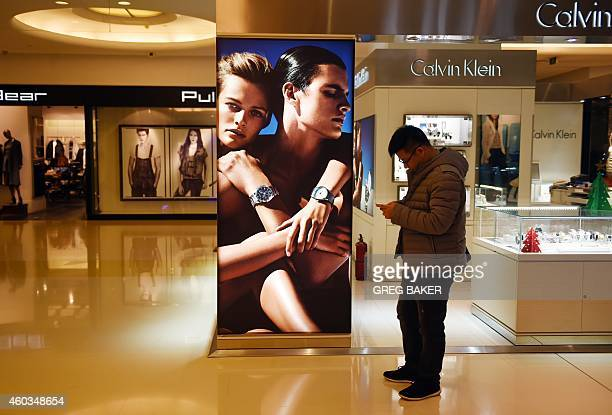 A man uses a smart phone in a shopping mall in Beijing on December 12 2014 Retail sales a key indicator of consumer spending increased 117 percent in...