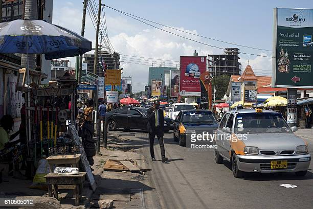 A man uses a smartphone as he walks along a busy highway in Accra Ghana on Monday Sept 19 2016 Ghana's central bank expects mergers and acquisitions...