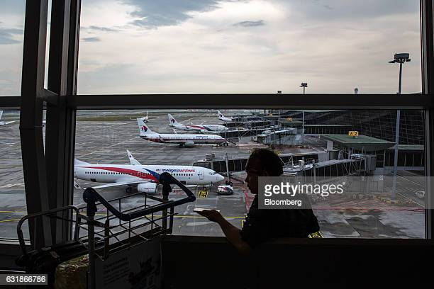 A man uses a smartphone in front of a window while Malaysian Airlines Bhd aircraft stand on the tarmac at Kuala Lumpur International Airport in...