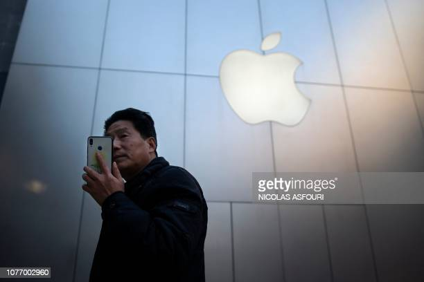 TOPSHOT A man uses a smartphone outside an Apple store in Beijing on January 4 2019 Apple cut its revenue outlook for the latest quarter on January 3...