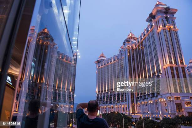 A man uses a smartphone takes a photograph of the Galaxy Macau Phase 2 casino and hotel developed by Galaxy Entertainment Group Ltd in Macau China on...