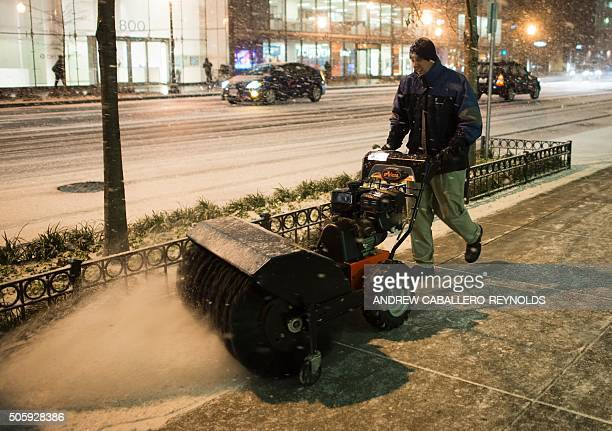 A man uses a snow blower to clear the sidewalk of snow in Washington DC on January 20 2016 / AFP / Andrew CaballeroReynolds