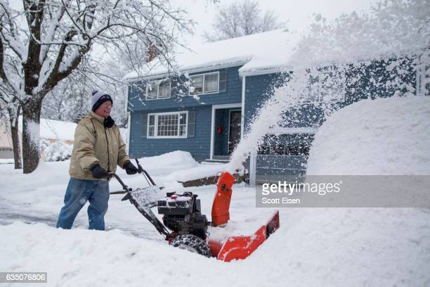A man uses a snowblower to clear his driveway during a snow storm February 13 2017 in Lynnfield Massachusetts Another winter storm has brought heavy...
