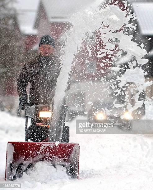 A man uses a snowblower to clear snow from the sidewalk on December 30 2011 in Oberhof eastern Germany Temperatures will stay at freezing point the...