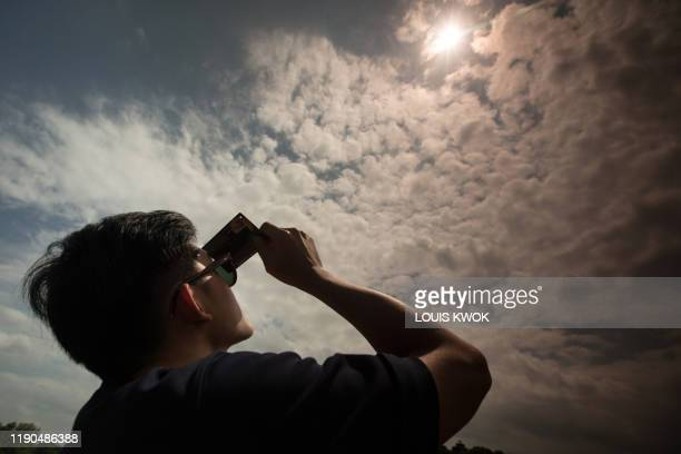 A man uses a solar filter to watch as the moon moves in front of the sun in a rare ring of fire solar eclipse in Singapore on December 26 2019