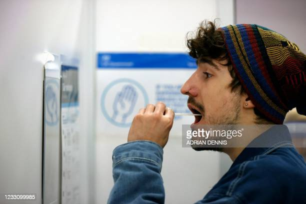 Man uses a swab to take a sample from his mouth at a NHS Test and Trace Covid-19 testing unit at the Civic Centre in Uxbridge, Hillingdon, west...
